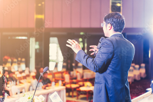 Fotografie, Obraz Asian businessman giving speech presentation stage meeting hall conference profe
