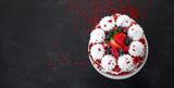 Delicious homemade red velvet cake with meringue and mascarpone cream on black background.