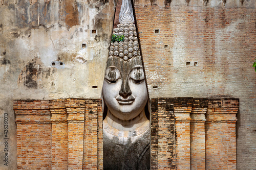 Fotografie, Obraz Ancient buddha statue Wat Si Chum temple in Sukhothai historical park Sukhothai,