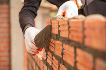 Close Up Hand Of Industrial Bricklayer In Glove Installing Bricks On Construction Site