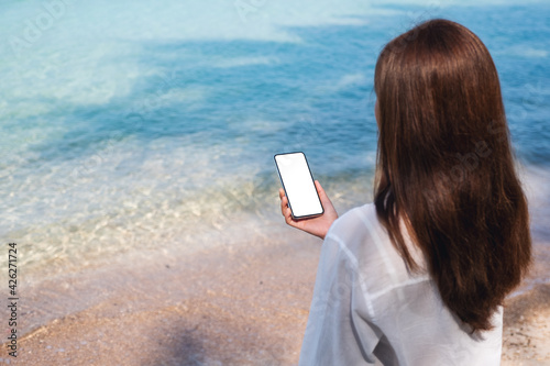 Rear view mockup image of a woman holding mobile phone with blank desktop screen while sitting on the beach