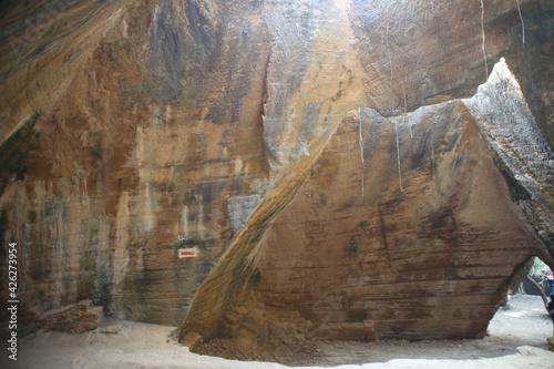 Ancient cave with the sunlight falling on the rocks Fotobehang
