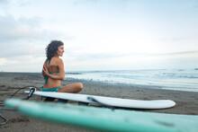 Woman Doing Baddha Konasana Facing The Ocean With Surf Boards On Balian Beach In Bali.