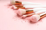 Fototapeta Kawa jest smaczna - Different makeup brushes with crushed cosmetic product on pink background, closeup. Space for text