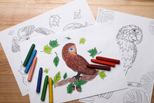 Colored And Blank Drawings With Crayons On Wooden Table, Flat Lay