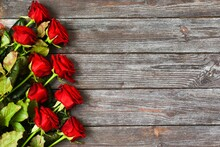 Bouquet Of Red Roses On A Wooden Background. A Greeting Card. Space For Text, Top View. Mothers Day. Valentines Day. Womans Day. Happy Birhday.