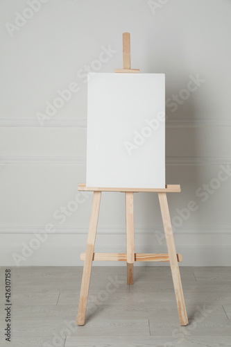 Wooden easel with blank canvas near light wall Fototapet