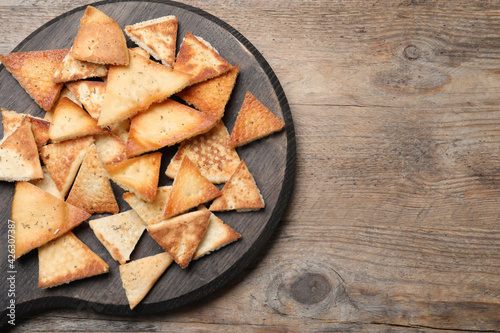 Delicious pita chips on wooden table, top view. Space for text