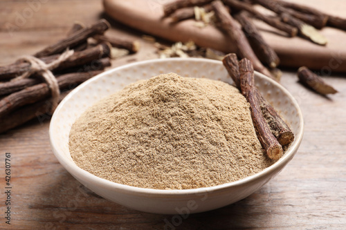 Dried sticks of liquorice root and powder on wooden table, closeup