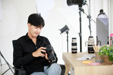 Asian Young Handsome Happy Male Short Black Hair Photographer Wears Long Sleeve Shirt And Jeans Hold Big DSLR Camera In Hands Sit On Chair In Photography Studio