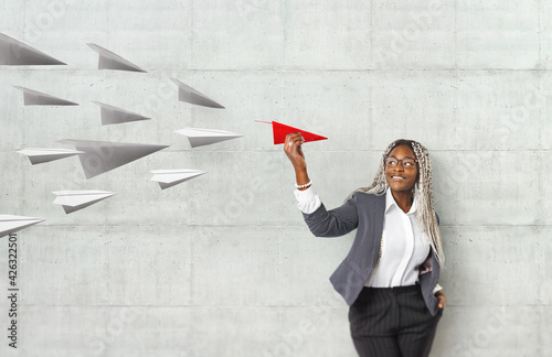 Young beautiful african woman holding hand model paper air plane. Design of travel concept with air plane on empty gray color background