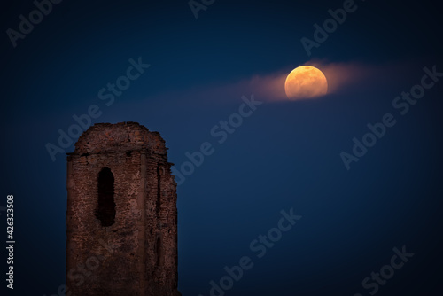 the ruins of the church tower and the moonrise in full moon Fototapet