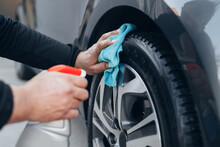 Close Up Man Cleaning Car Tires In Carwash Service