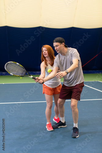 Canvas Tennis player getting instruction from coach how to play game on a court indoor