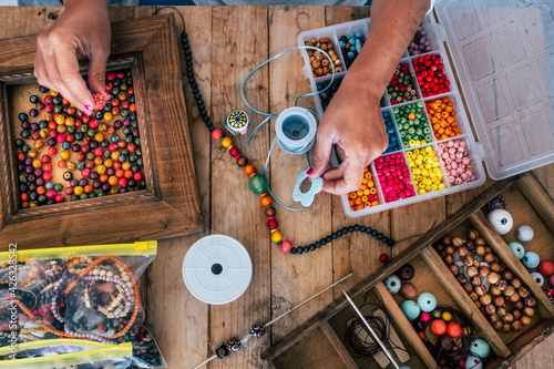 Obraz Making of handmade jewellery. Box with beads on old wooden table. Top view with woman hands - tutorial to learn how to make bracelets and jewellery online and alternative home job - fototapety do salonu