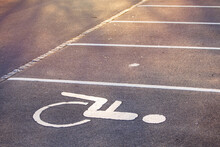 Empty Parking Lot, White Lines On The Asphalt, Sunny Day. Handicapped Parking Space At A Parking Lot Outside A Building, Icon, Sign Painted On The Designated Parking Space For Disabled Persons.