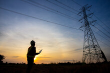 Silhouette Of Electrical Engineer Or Technician Standing And Watching At The Electric Power Station To View The Planning Work By Producing Electricity At High Voltage Electricity Poles At The Sunset.