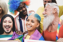 Multiracial Gay People Having Fun At Pride Parade With LGBT Flags And Banners Outdoors - Main Focus On Lesbian Face