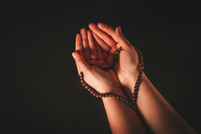 Female Hands With Prayer Wooden Rosary On A Dark Background. Beautiful Background For The Celebration Of The Holy Muslim Month Of Ramadan Kareem