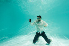 Arabian Businessman In Formal Wear And Goggles Holding Smartphone With Blank Screen Underwater