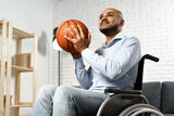Happy young disabled man in wheelchair holding basketball ball and smiling