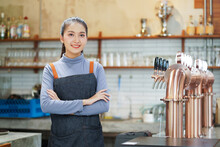 Beautiful Bartender Or Business Owner In Apron Post Portrait Looking At Camera And Smiling While Standing Near The Bar Counter Beer Tap In Pub And Restaurant