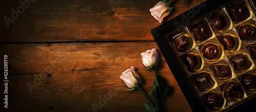 romantic gift - chocolate candy box with rose flowers on old wooden background. banner copy space