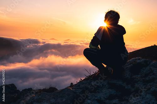 Obraz Niño senderista  disfrutando del atardecer en lo alto de la montaña. Hiker boy enjoying the sunset at the top of the mountain.  - fototapety do salonu