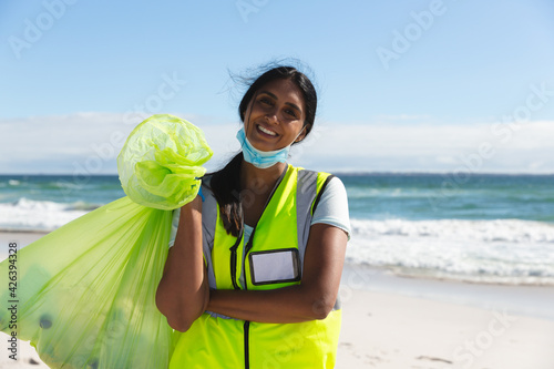 Portrait of happy mixed race woman wearing face mask collecting rubbish from the beach