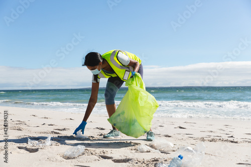 Mixed race woman wearing face mask collecting rubbish from the beach