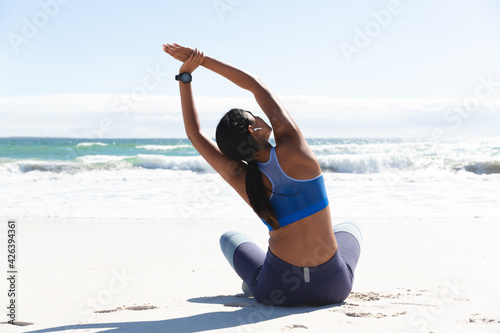 Mixed race woman exercising on beach sitting and stretching