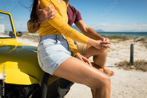 Midsection of happy caucasian couple sitting on beach buggy by the sea holding hands
