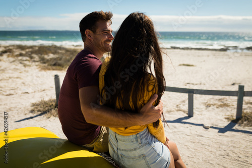 Happy caucasian couple sitting on beach buggy by the sea embracing