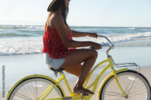Happy mixed race woman on beach holiday riding bicycle