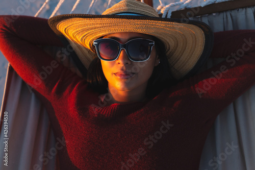 Portrait of happy mixed race woman on beach holiday looking to camera lying in hammock during sunset