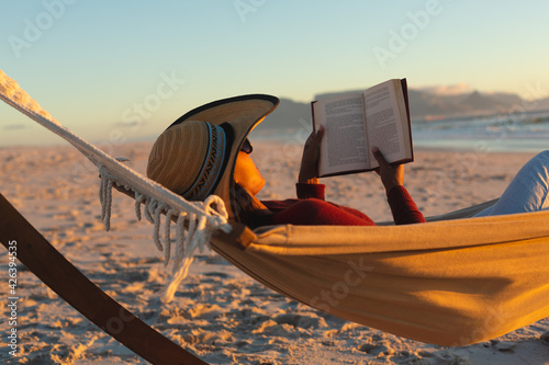 Mixed race woman on beach holiday lying in hammock reading book during sunset