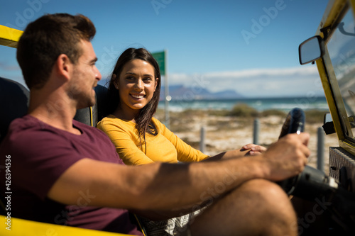 Happy caucasian couple sitting in beach buggy by the sea talking