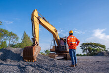 Driver Excavator For Road Construction, Crawler Excavator In Construction Site On Blue Sky Background