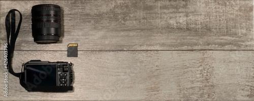 cámara, objetivo y tarjeta sd en un fondo de madera