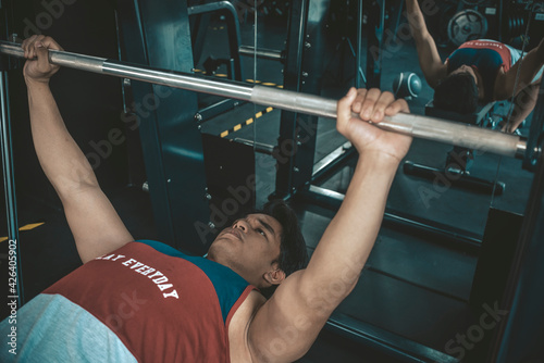 Tela A young man with a year of training experience doing bench presses on a smith machine