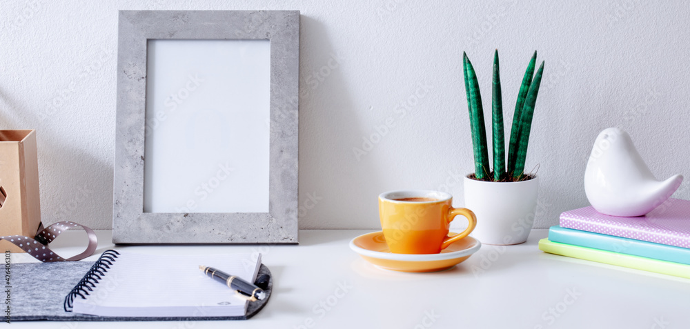 Fototapeta Cozy home office on white  table , fountain pen, ribbon, yellow cup of coffee, frame with space for tekst,  notebook  Background with copy space. Elegant feminine workspace.