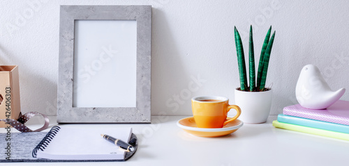 Obraz Cozy home office on white  table , fountain pen, ribbon, yellow cup of coffee, frame with space for tekst,  notebook  Background with copy space. Elegant feminine workspace.  - fototapety do salonu