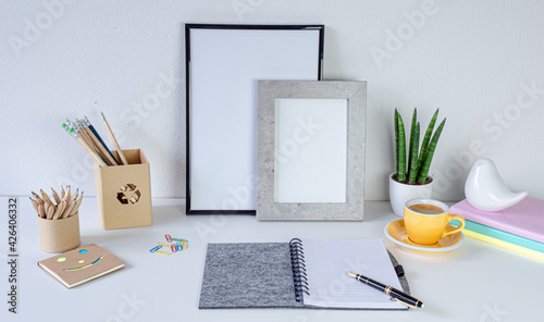 Obraz Workspace home office. Cozy home office on white table , fountain pen,  yellow cup of coffee, frame with space for tekst, notebook Background with copy space. Elegant feminine workspace.  - fototapety do salonu