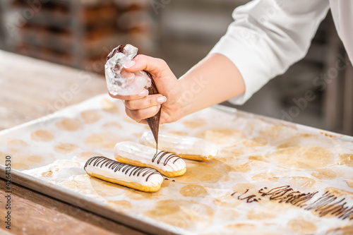 Fotografie, Obraz Hand decorating eclair with chocolate using pastry bag