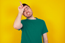Young Caucasian Man Wearing Green T-shirt Against Yellow Wall Making Fun Of People With Fingers On Forehead Doing Loser Gesture Mocking And Insulting.