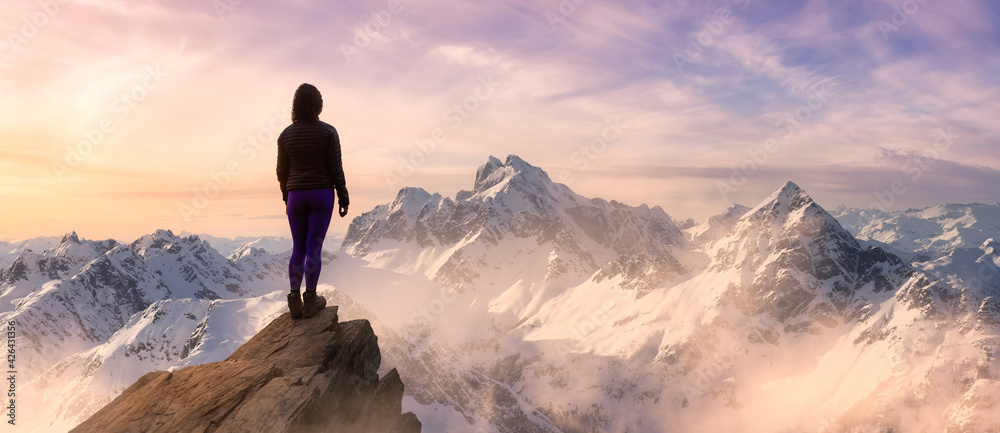 Fototapeta Fantasy Adventure Composite with a Girl on top of a Mountain Cliff with Dramatic Landscape in Background. Landscape from British Columbia, Canada. Pink Sunset Sky.