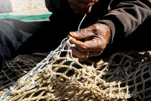 Old Fisherman Hand Sews A Fishing Net