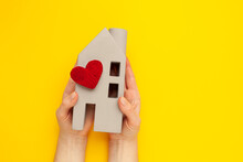 Orphanage. Figure Of A House With A Heart In His Hands On A Yellow Background. Nursing Home Concept.