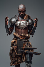 Authentic African Barbarian Prays With Raised Hands In Gray Background