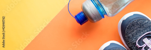 Fototapeta Sport equipment,blue Sneakers, water, on orange background, Flat lay.shoes, skipping rope and bottle of water. Concept of healthy lifestile, everyday training and force of will.Web banner obraz